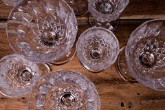 Finely chiseled crystal glasses, flat top view from above on woo. Den table; elegant stemware stock photo