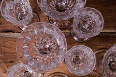 Finely chiseled crystal glasses, flat top view from above on woo. Den table; elegant stemware stock photography