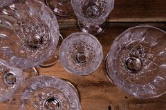 Finely chiseled crystal glasses, flat top view from above on woo. Den table; elegant stemware stock photos