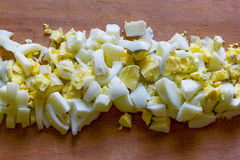 Finely chopped boiled eggs in the middle of an old wooden cutting board Stock Photos