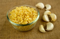 Finely chopped garlic with cloves in the background Royalty Free Stock Image
