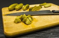 Chopped pickled cucumbers on a chopping board. Finely chopped pickled cucumbers for a vegetable salad on a chopping board Royalty Free Stock Photo