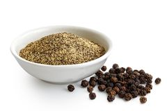 Finely ground black pepper in white ceramic bowl isolated on white. Black peppercorns. stock photography