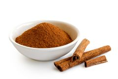 Finely ground cinnamon in white ceramic bowl isolated on white. Cinnamon sticks royalty free stock image