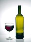 Finendo la bottiglia - il vetro del vino rosso e si avvicina alla bottiglia vuota Fotografia Stock