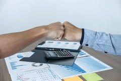 Finendo su una riunione, dante primo urto della gente di affari felice della mano due dopo l'accordo di contratto trasformarsi in immagine stock