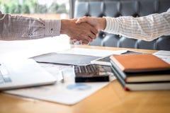Finendo su una riunione, una stretta di mano di due genti di affari felici dopo l'accordo di contratto trasformarsi in in un part immagini stock