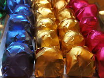 Finest chocolate gathering in bright. Red, blue, golden and green wrapper Stock Photography