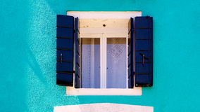 Finestra blu in Burano sulla parete blu di ccolor immagine stock libera da diritti
