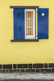 Finestra blu con i cuori e la parete gialla Immagine Stock