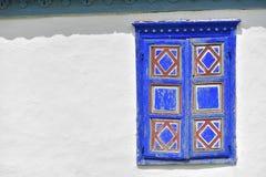 Finestra blu e rossa d'annata chiusa sulla parete bianca di vecchio traditio Fotografia Stock Libera da Diritti