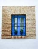 Finestra blu in muro di mattoni dentro un patio Cordovan, con i vasi da fiori immagini stock libere da diritti