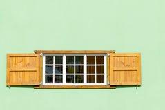 Finestra caraibica variopinta ed otturatori in una parete verde Immagini Stock