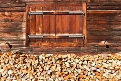Finestra chiusa e legna da ardere impilata di vecchia capanna alpina Paesaggio alpino rurale Fotografie Stock