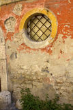 Finestra circolare con la griglia del ferro in vecchia parete del gesso a Benevento, campania, Italia Immagini Stock