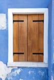 Finestra con gli otturatori di legno sulla parete blu Immagini Stock Libere da Diritti