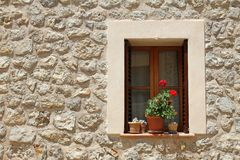 Finestra con i vasi da fiori sulla parete di pietra Fotografia Stock