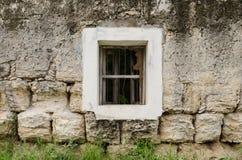 Finestra con la struttura bianca su una parete delle pietre polverose ed arrugginite immagine stock