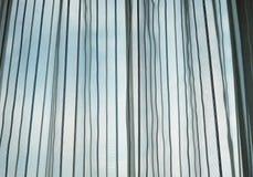 Finestra con la tenda ed il cielo blu Fotografia Stock Libera da Diritti