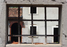 Finestra con le barre di metallo che incorniciano una casa dell'azienda agricola di abbandono Fotografia Stock Libera da Diritti