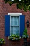 Finestra con le imposte blu con il contenitore di fiore Fotografie Stock