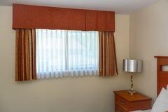 Finestra con le tende ed il comodino nell'angolo della stanza fotografie stock