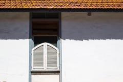 Finestra con un otturatore e un'ombra del tetto Immagine Stock