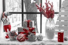 Finestra decorata con le decorazioni di Natale con i contenitori di regalo, i ramoscelli, l'abete rosso e le palle Colore rosso s fotografia stock libera da diritti