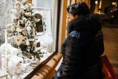Finestra del negozio di Natale ammirata dalla donna Fotografia Stock