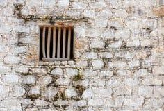 Finestra della cella di prigione con le barre di legno in un muro di mattoni bianco Fotografia Stock Libera da Diritti