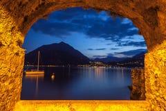 Finestra della roccia sopra il lago tranquillo Como al crepuscolo Immagine Stock