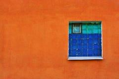 Finestra delle mattonelle verdi e blu in una parete arancio del gesso immagini stock