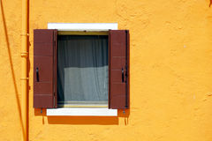 Finestra di Brown in Burano sulla parete arancio di colore immagine stock