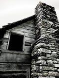 Finestra di cabina con il camino di pietra Fotografia Stock