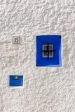 Finestra di legno blu iconica sulla parete di pietra bianca della casa greca tipica di stile, Immagine Stock