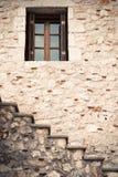 Finestra di legno e di vetro in una parete di pietra con le scale Immagine Stock