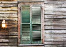 Finestra di legno rustica della costruzione con gli otturatori verdi chiusi e il lig Fotografia Stock