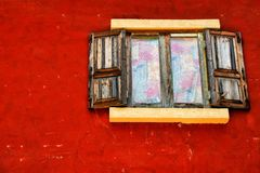 Finestra di legno sulla parete rossa Immagine Stock