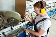 Finestra di plastica e fabbricazione della porta Lavoratore che taglia il profil del PVC Fotografie Stock