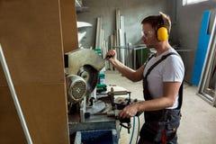 Finestra di plastica e fabbricazione della porta Lavoratore che taglia il profil del PVC Fotografia Stock