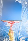 Finestra di pulizia con il cielo blu del seccatoio Fotografie Stock Libere da Diritti