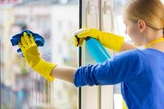 Finestra di pulizia della donna a casa Fotografie Stock Libere da Diritti