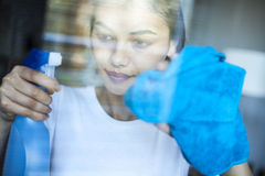 Finestra di pulizia della donna del ritratto nella casa immagini stock libere da diritti