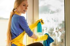 Finestra di pulizia della ragazza a casa facendo uso dello straccio detergente Fotografie Stock