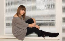 finestra di seduta del brunette Fotografie Stock Libere da Diritti