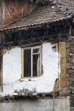 Finestra di vecchia povera casa con i vasi della pianta sotto la pioggia, villaggio di Pirin in montagne di Pirin, Bulgaria, dett fotografia stock libera da diritti