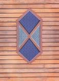 Finestra di vetro macchiato blu scuro e grigia d'annata sulla parete di legno nel fondo orizzontale fotografie stock libere da diritti