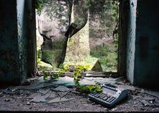 Finestra distrutta in costruzione abbandonata con l'edera e un registratore di cassa rotto fotografie stock