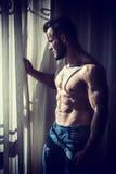 Finestra facente una pausa dell'uomo topless muscolare immagine stock