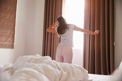 Finestra facente una pausa della camera da letto della donna nella mattina e nell'allungamento Fotografie Stock